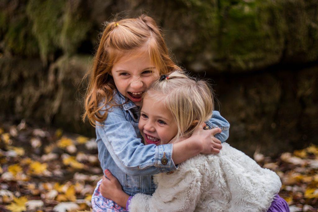 little girls hugging outdoors