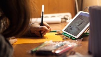 Girl working on homework in front of an ipad.