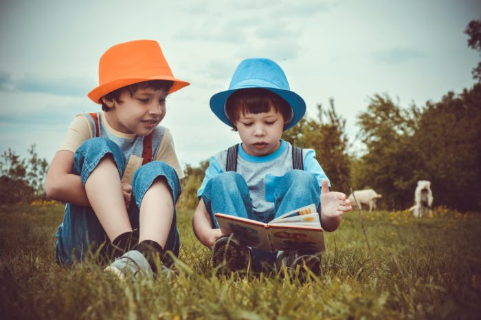 boys reading on the grass