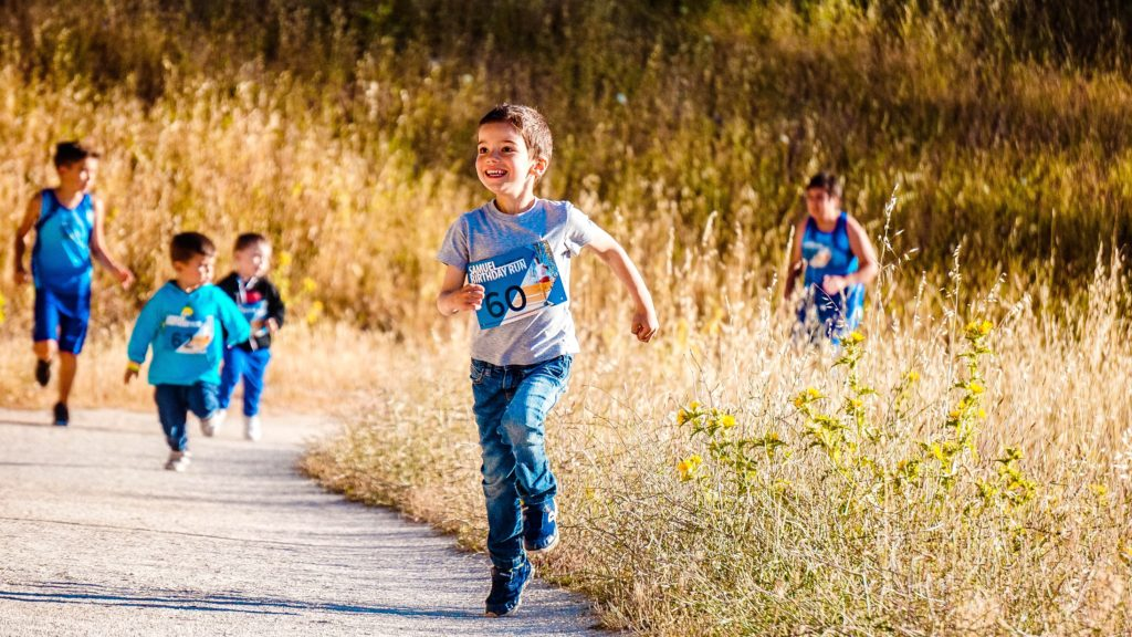 A smiling boy runs on a track through a field while other children run behind him.
