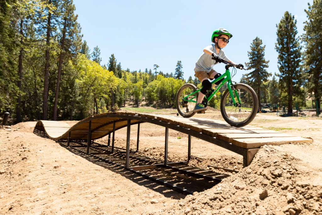 A boy wearing sunglasses, a helmet, and knee pads rides a bike over a wooden bridge on a dirt trail.