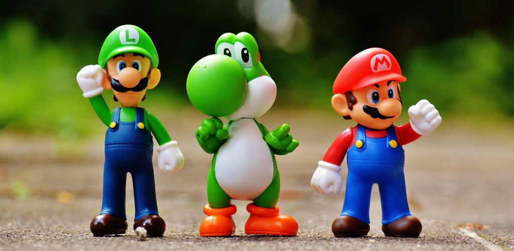 close up photo of plastic Mario, Luigi, and Yoshi character figurines