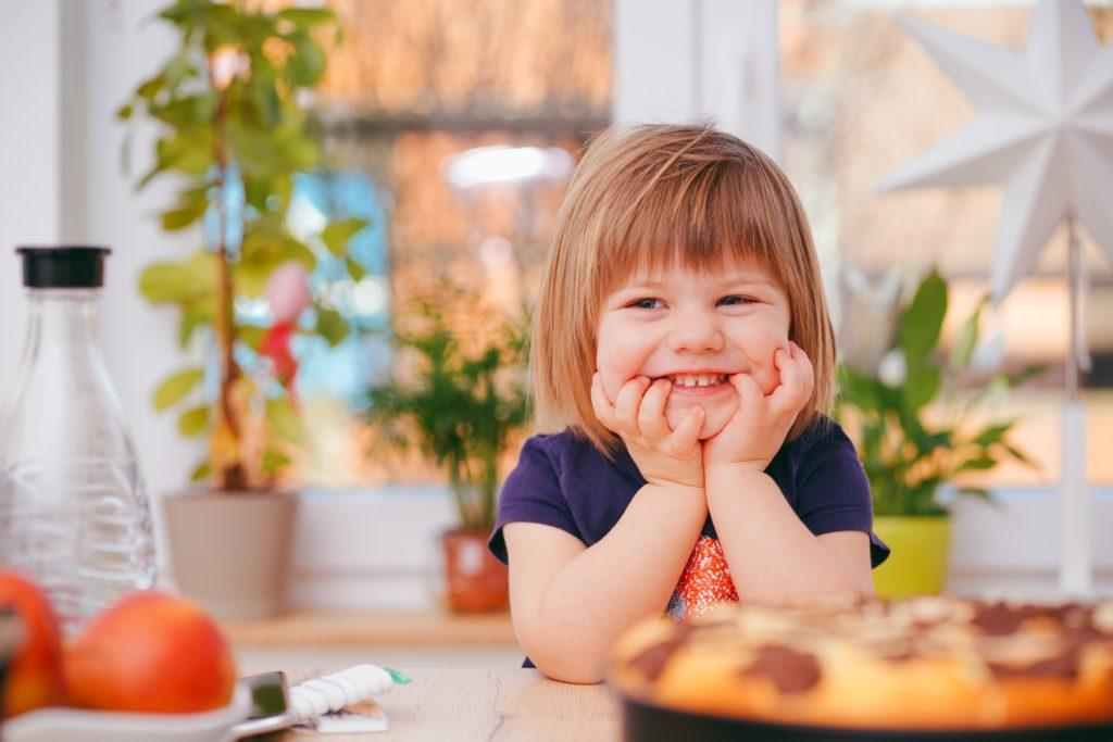 toddler sitting at kitchen table, smiling