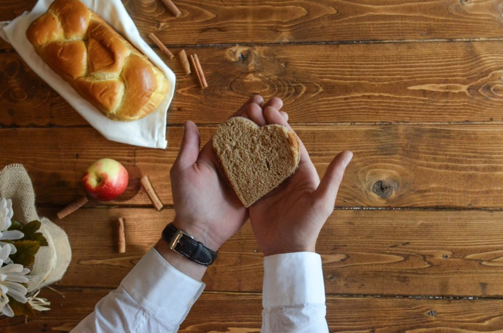 A pair of hands hold a heart-shaped piece of bread over a table with a loaf of bread, an apple, and cinnamon sticks