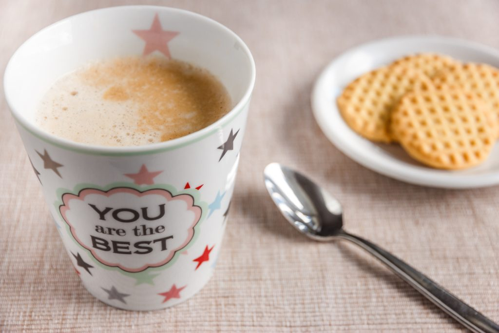 "A coffee mug that says ""You are the best"" next to a spoon and a plate of cookies"