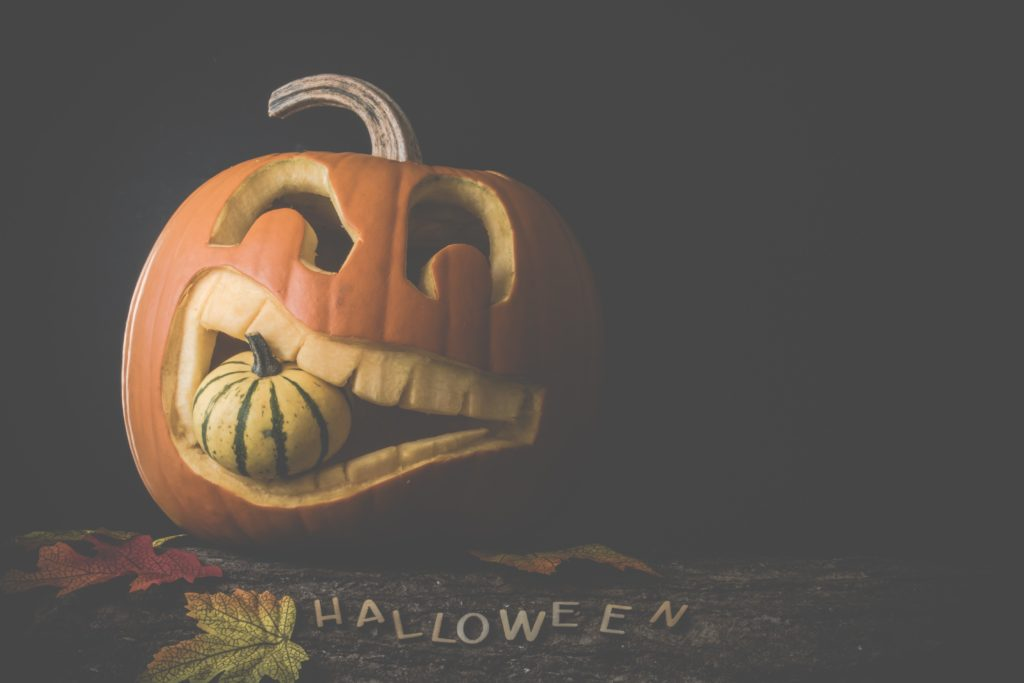 jack o' lantern with a smaller pumpkin in its mouth on a wooden surface with the word Halloween in capital letters on the wood