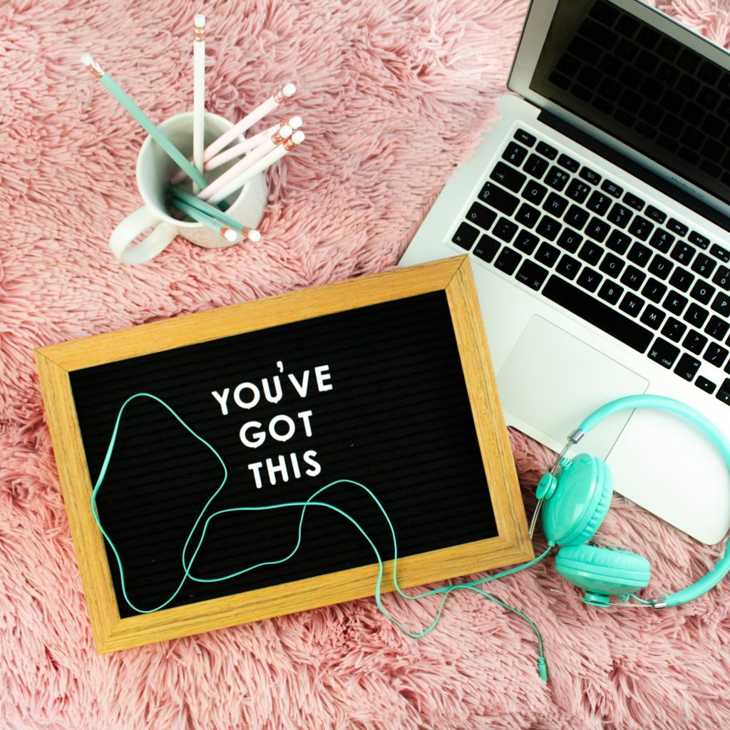 "A board that reads ""YOU'VE GOT THIS"" next to a laptop, pencil cup, and headphones"