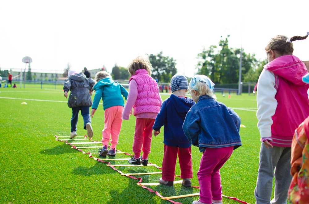 Children outside hopping through a rope ladder