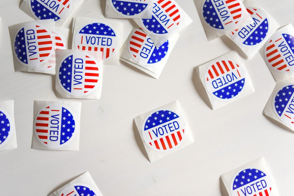 "A bunch of ""I Voted"" stickers on a white background"