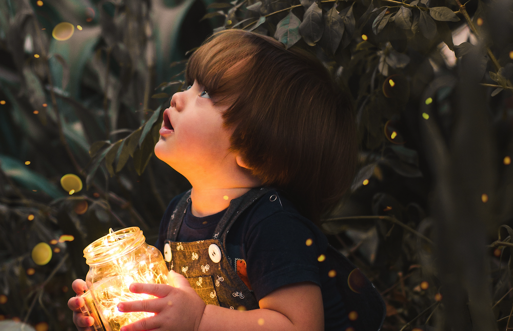 Child holding jar full of lights