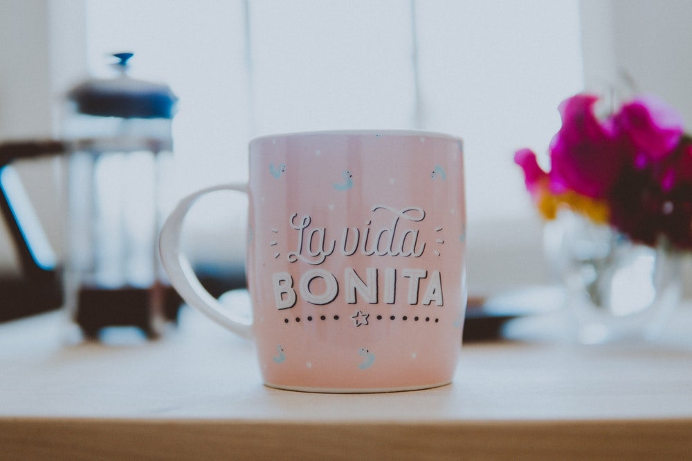 "Pink coffee mug that says ""La vida bonita"""