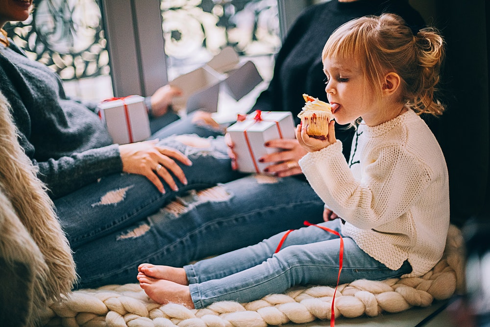 Girl eating a cupcake surrounded by cookies