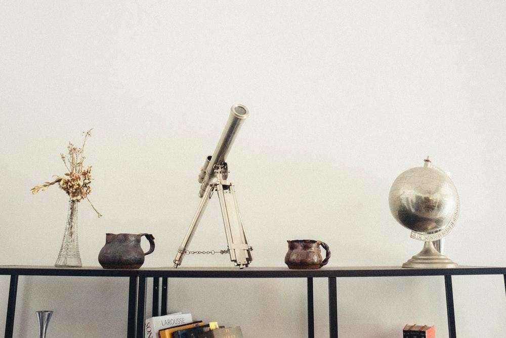 Silver telescope on desk next to globe