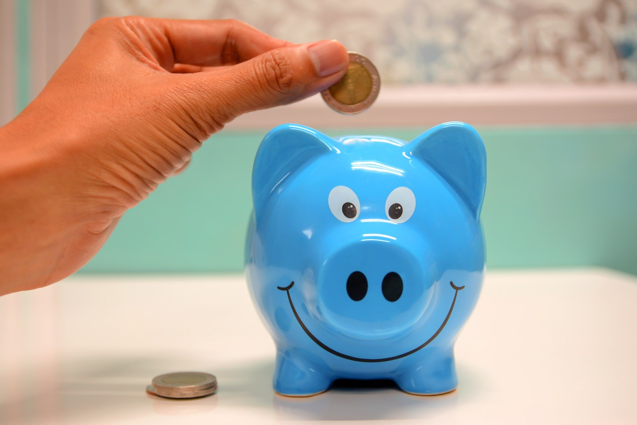 Person placing a coin into a blue piggy bank