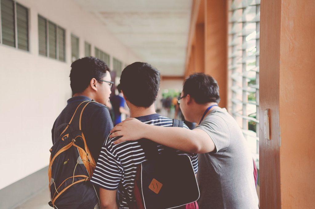 Group of friends walking down a hallway wearing backpacks