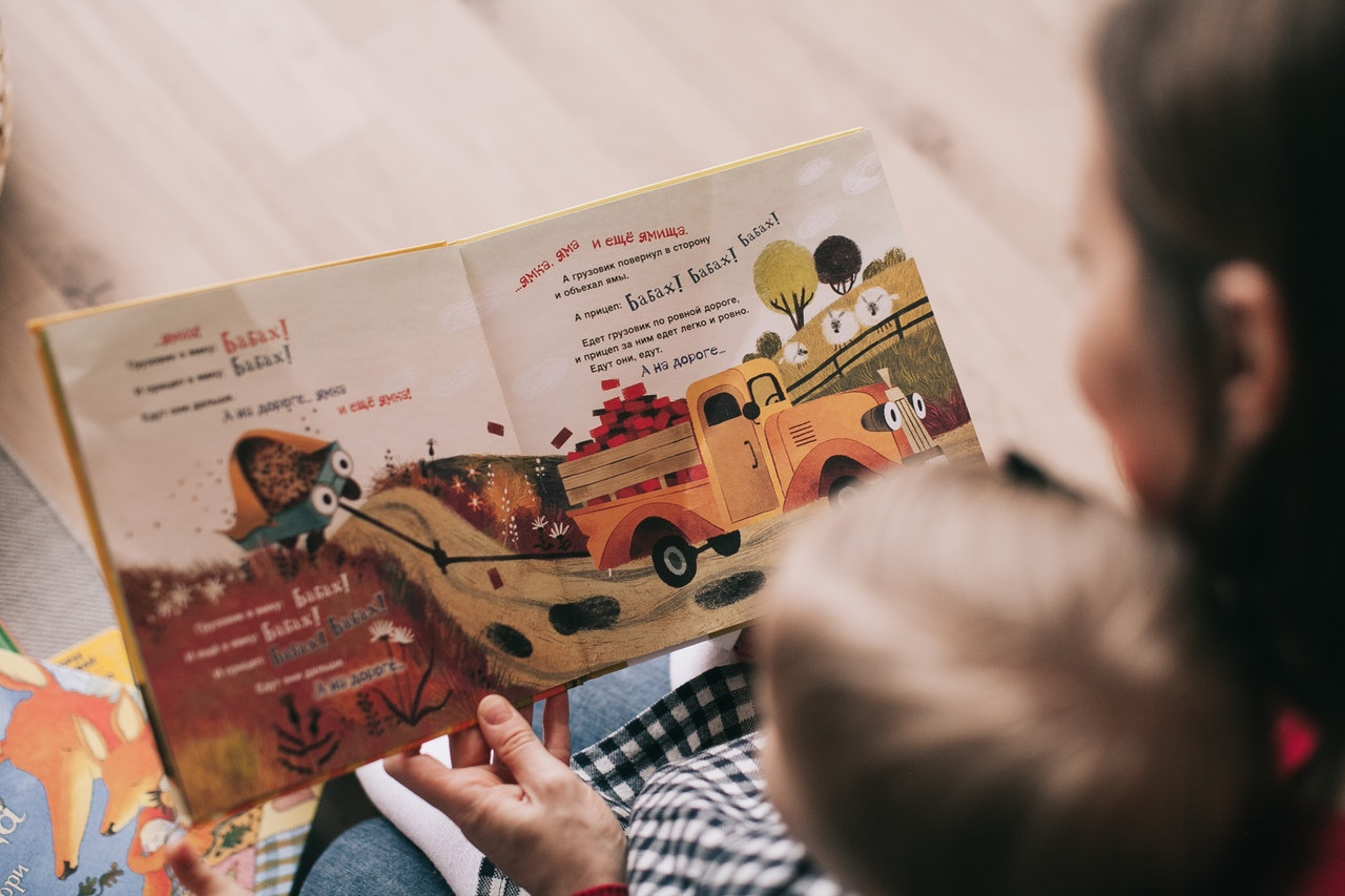 Woman reading a kid's book to her son