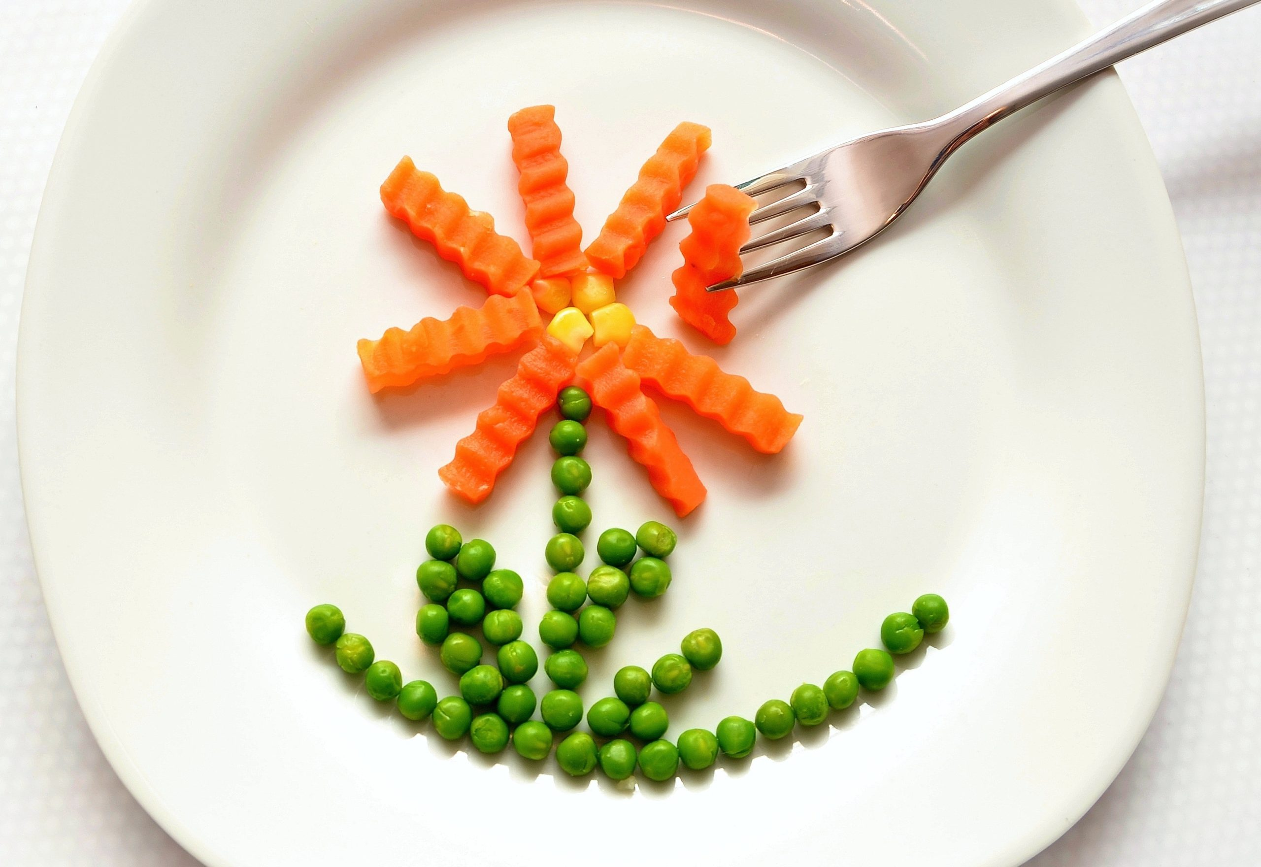Carrots and peas on a white plate making a flower