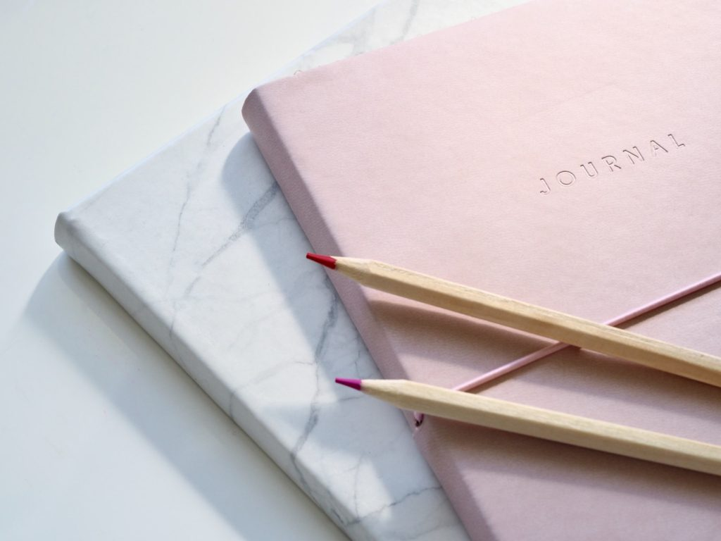 Pink journal and colored pencils