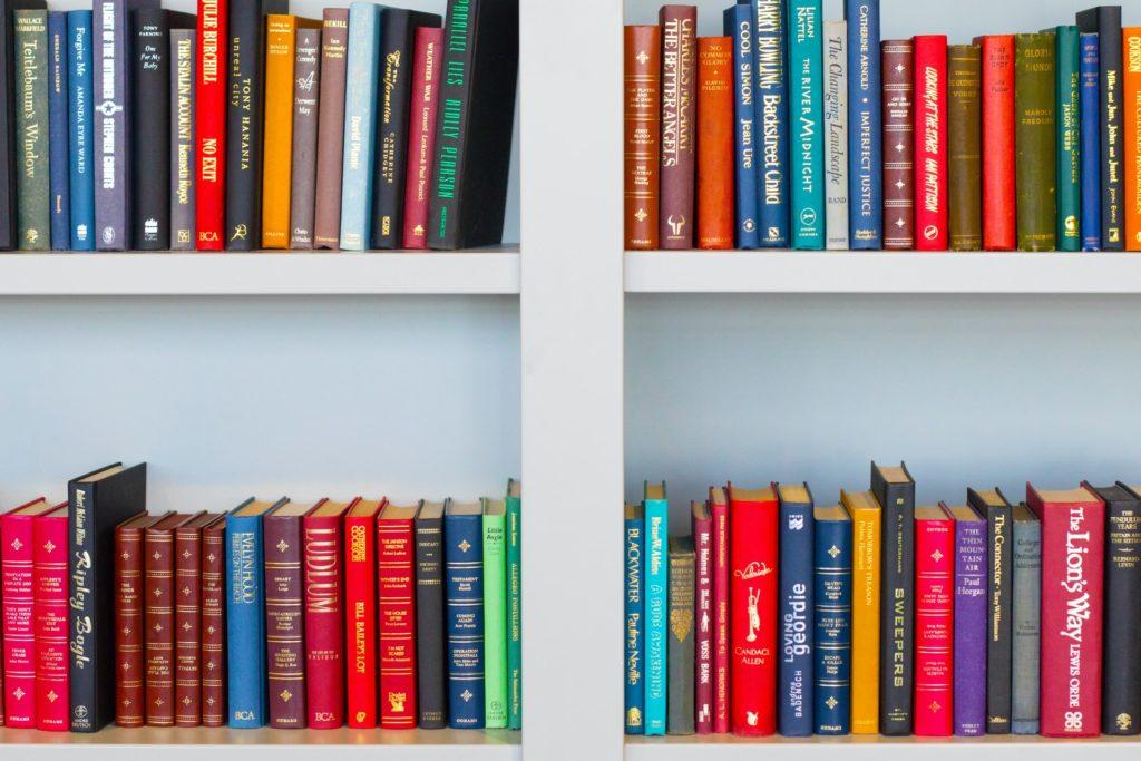 Colorful books on a white bookshelf.