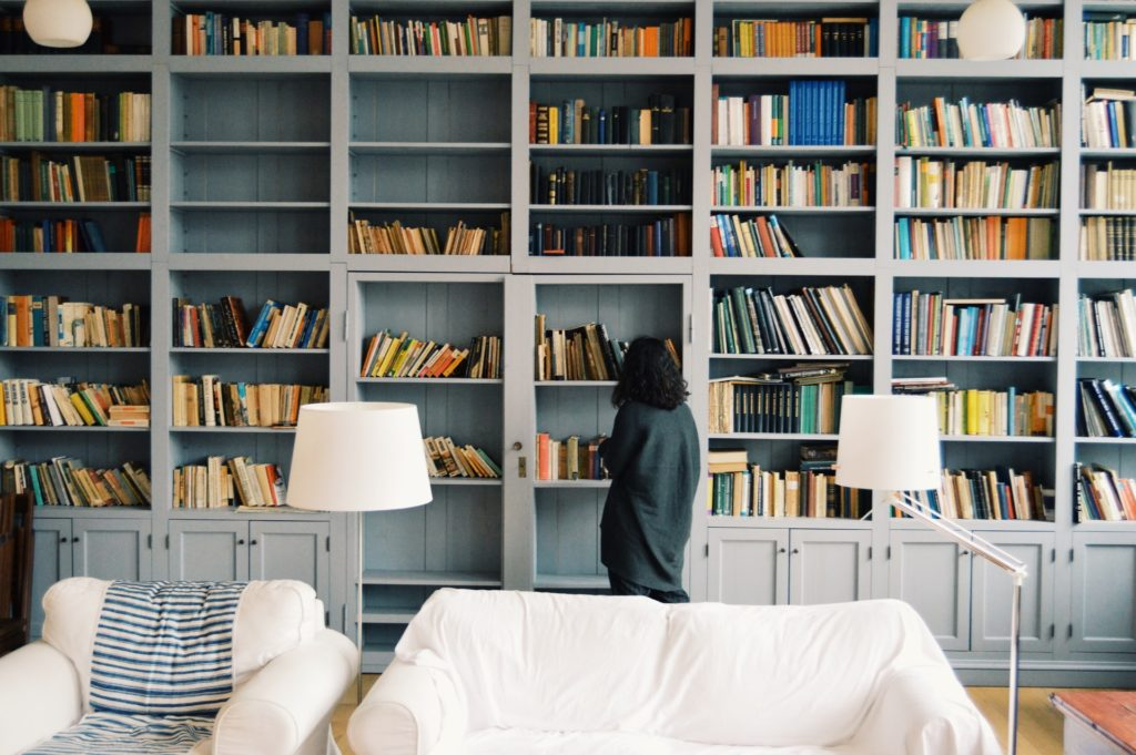 Girl standing in front of a wall of books
