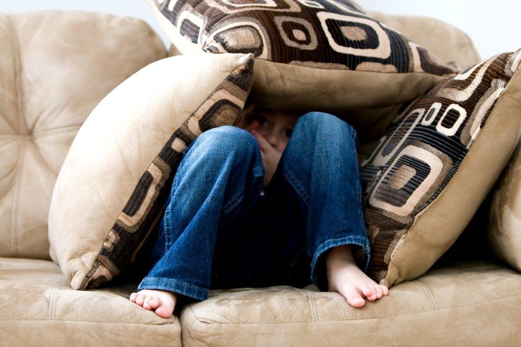 Boy hiding in pillows