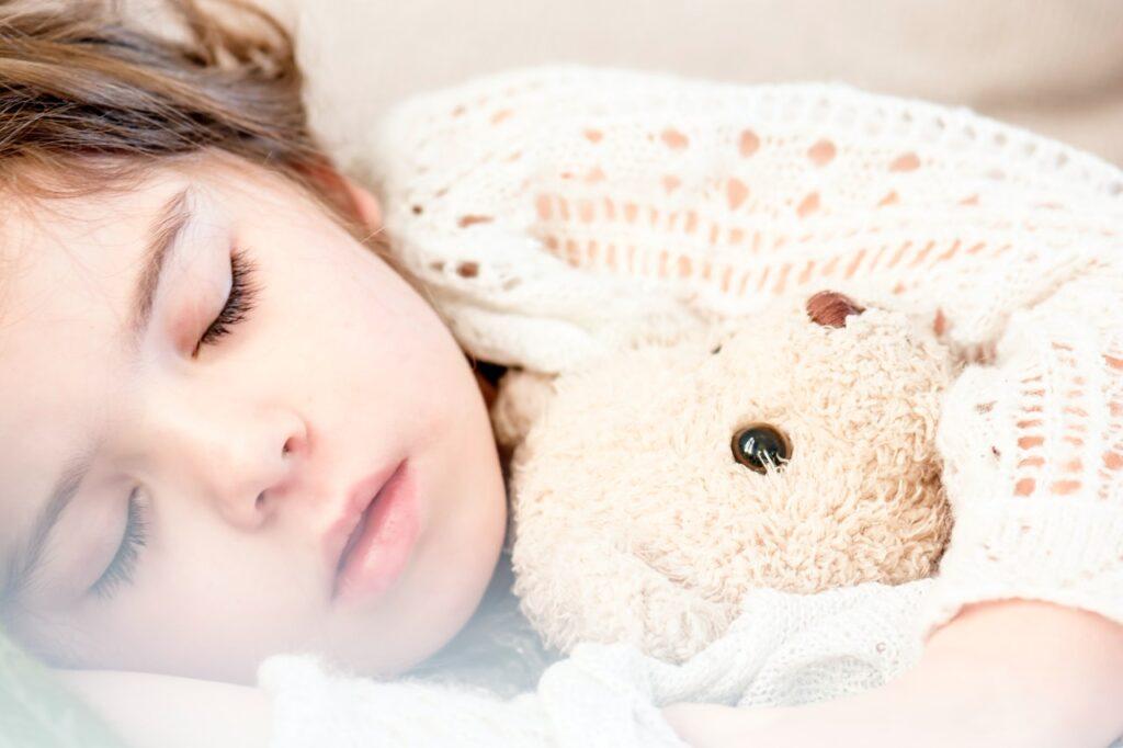 Girl sleeping with a teddy bear